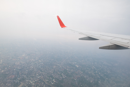 Aircraft wing flying view from window of city in the morning. Traveling concept. Wing of an aircraft.