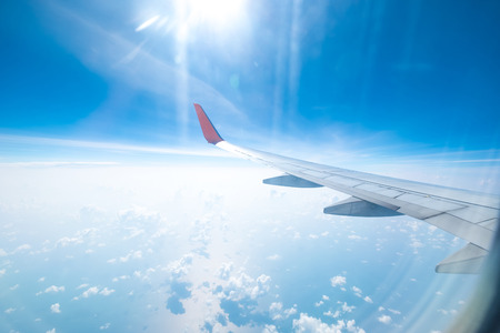 Aircraft wing flying above the beautiful clouds with sunlight in the morning. Traveling concept. Wing of an aircraft