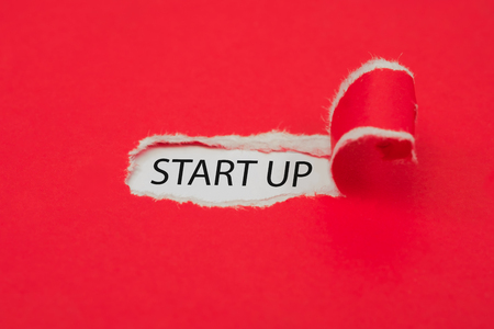 Torn red paper revealing the word start up concept.