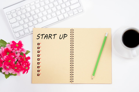 Note book with start up word and check marks, keyboard, red flower, pencil and a cup of coffee on white table background. Stock Photo