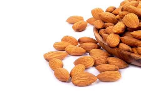 Almonds in wooden dish on white background.