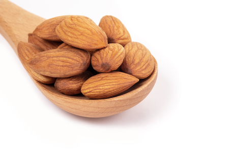 Almonds in wooden spoon on white background.