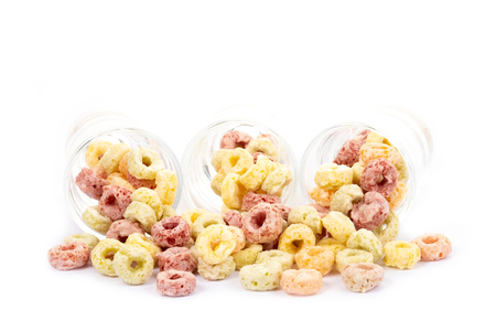Colorful cereal loop rings on white background. Healthy and funny addition to kids breakfast Stock Photo
