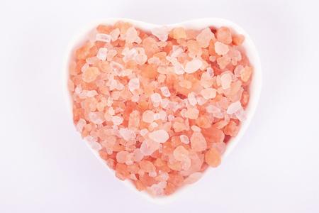 Himalayan Pink Salt in bowl ceramic heart shape. Health concept. Stock Photo