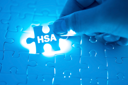 Doctor hand holding a jigsaw puzzle with HSA (Health Savings Account). Medical concept Stock Photo