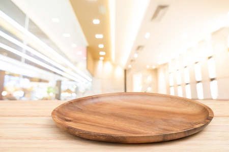 Perspective wooden table and wooden tray on top over blur bokeh light background, can be used mock up for montage products display or design layout. Stock Photo