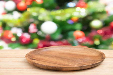 Perspective empty wooden tray table and christmas tree blur decoration background, for product display montage or design layout.