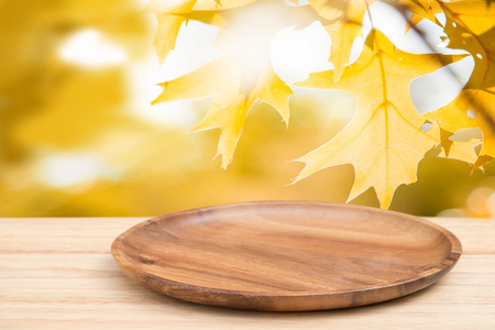 Perspective wooden table on top over blur natural of maple leaf background, can be used mock up for montage products display or design layout.