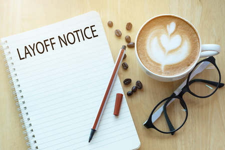 layoff notice word on notebook with glasses, pencil and coffee cup on wooden table. Business concept.