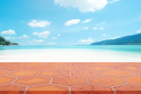 Perspective empty mon brick flooring (clay brick) on top over blur sea in sunny day background.