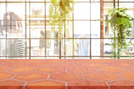 Perspective empty mon brick flooring (clay brick) over blurred shopping mall background, for product display montage or design layout.