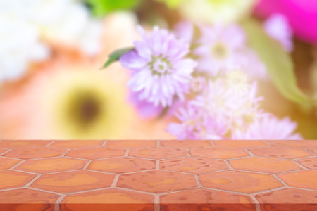 Perspective empty mon brick flooring (clay brick)  blur flower background, can be used mock up for montage products display or design layout.