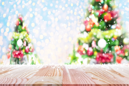 Perspective empty wooden table with blur christmas tree and snow flake background. For product display montage or design layout.