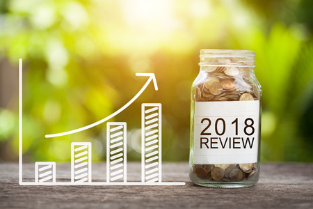 2018 review word with coin in glass jar and graph up. financial concept Stock Photo