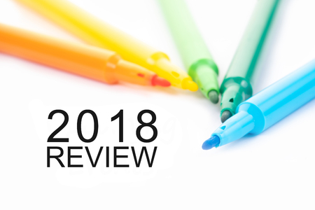 Colorful felt-tip pen and 2018 review word on white background.