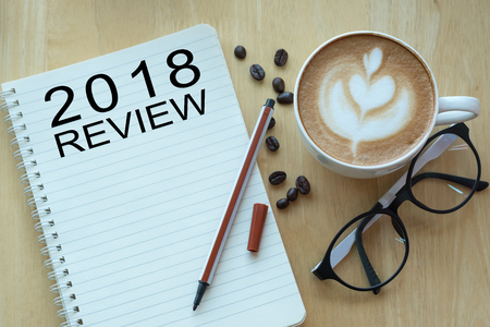 2018 review message on notebook with glasses, pencil and coffee cup on wooden table.