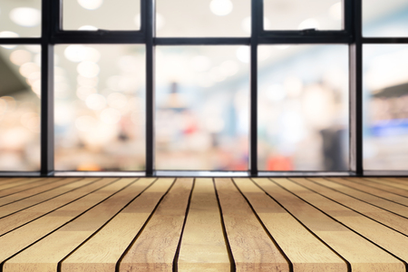 Perspective wooden board empty table on top over blurred coffee shop background, can be used mock up for display of product or design layout. Stock Photo