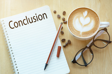 Conclusion word on notebook with glasses, pencil and coffee cup on wooden table. Business concept. Stock Photo