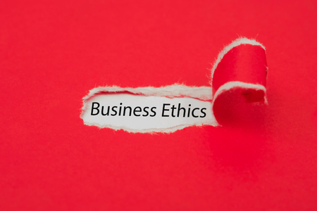 Torn red paper revealing the business ethics word. Business concept