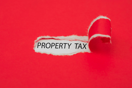 Torn red paper revealing the word events. Property Tax concept.