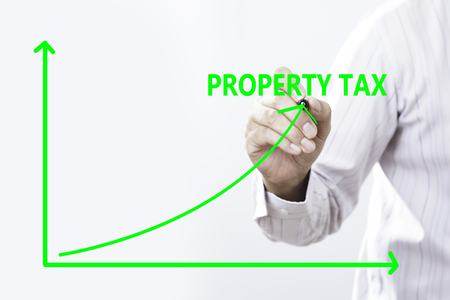 Property Tax Text With Businessman Hand Point On Virtual Graph Green line. Stock Photo