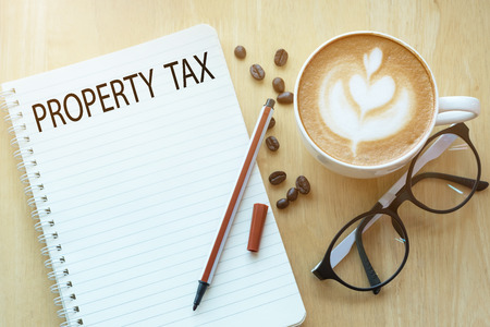 Property Tax concept on notebook with glasses, pencil and coffee cup on wooden table. Business concept.