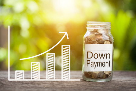 Down Payment Word With Coin In Glass Jar and graph up. Financial Concept.