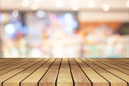 Perspective wooden table on top over blur coffee shop background, can be used mock up for montage products display or design layout.