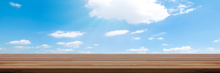 Perspective wooden table on top over blur sky background, can be used mock up for montage products display or design layout. Stock Photo