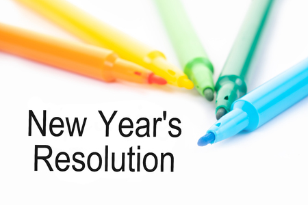 Colorful felt-tip pen and New Year's Resolution words on white background.