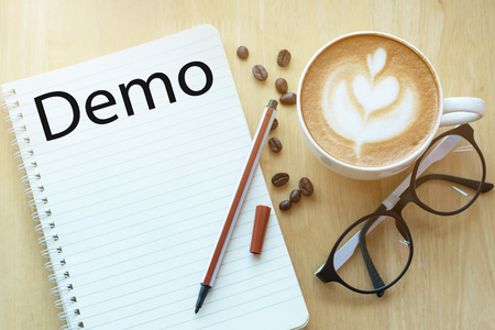 Demo concept on notebook with glasses, pencil and coffee cup on wooden table. Business concept.