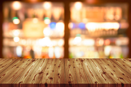 Empty wooden table top with blurred of coffee shop, cafe, bar background, Abstract background can be used for display or montage your products. Imagens