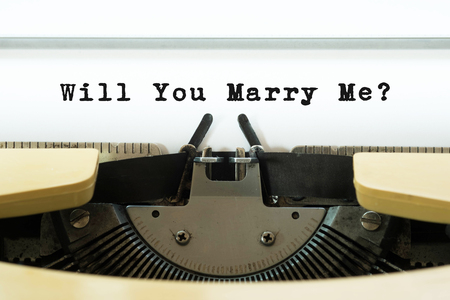Will you marry me word on a yellow vintage typewriter. Valentines day concept. Marriage and wedding proposal. Stock Photo