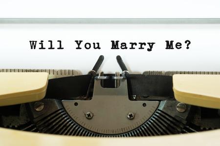 Willst du mich auf einer gelben Vintage-Schreibmaschine heiraten? Valentinstag-Konzept. Heirats- und Heiratsantrag. Standard-Bild