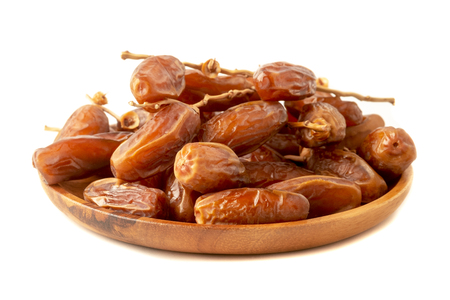 Close up of cluster dates plam. Fresh dates plam in wooden tray over white background.