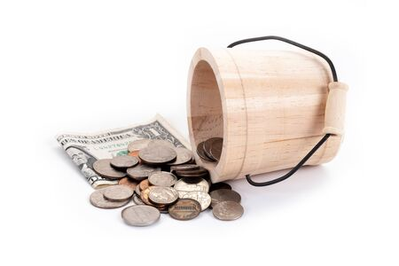 Wooden bucket and money, US Dollars bank notes, penny, nickel, dime, quarter on a white background. Time to invest, time value for money, money saving, finance saving and investment concept.
