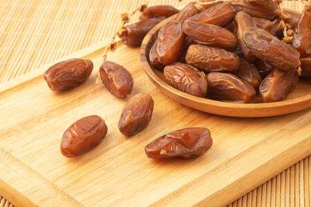 Close up of cluster dates plam. Fresh dates plam on wooden tray.
