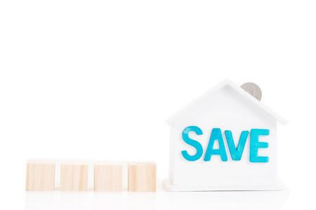 Wooden block and Save word on house is white Piggy bank with coins on white background.Time to invest, real estate and property concept. Finance saving and investment concept.
