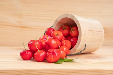 Acerola cherry in wooden bucket on wooden background. Select  focus, Barbados cherry, Malpighia emarginata, high vitamin . Acerola fruit.