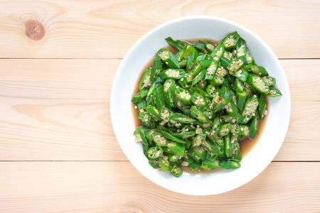 Okra fried in white plate on wooden background. Health food concept.