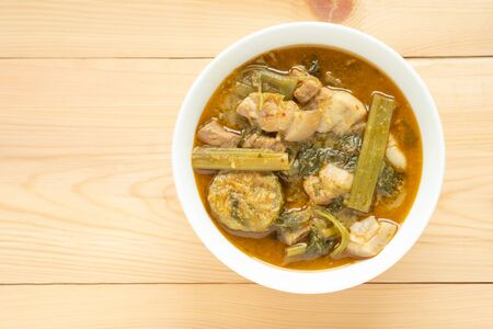 Pork curry with thai morning glory with Red Curry in white bowl on wooden background. Thai food.