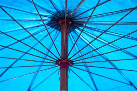 Close up view of the inside of an open, blue umbrella.