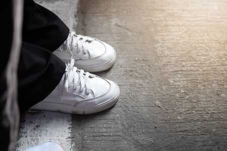 White sneakers on asphalt and sunlight in morning time. 写真素材