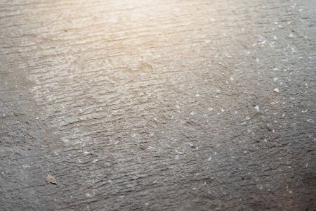 Dark grey asphalt pavement texture with small rocks and sunlight in the morning time. 写真素材