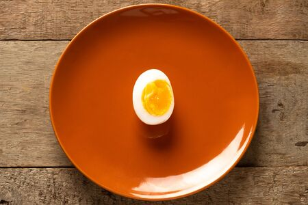 Medium-boiled eggs in a brown ceramic dish on a wooden table. Top view. Health concept. Imagens - 133374709