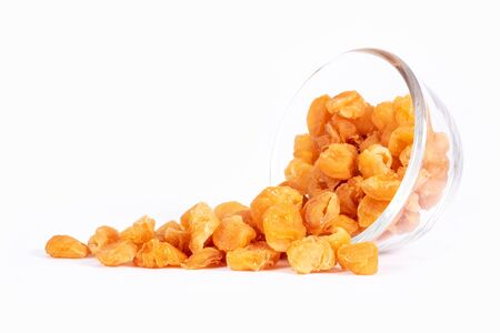 Golden dried longan fruit in glass bowl isolated on white background. Imagens