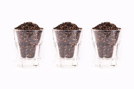 Close up organic black sesame seeds in glass on white background. Health food concept. Imagens