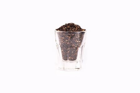 Close up organic black sesame seeds in glass on white background. Health food concept. Imagens - 133375873