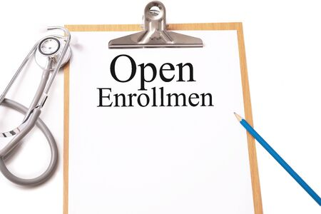 Stethoscope on notebook and pencil with Open Enrollment words as medical concept. Imagens