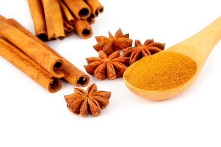 Star anise, Cinnamon sticks and powder in wooden spoon isolated on white background.